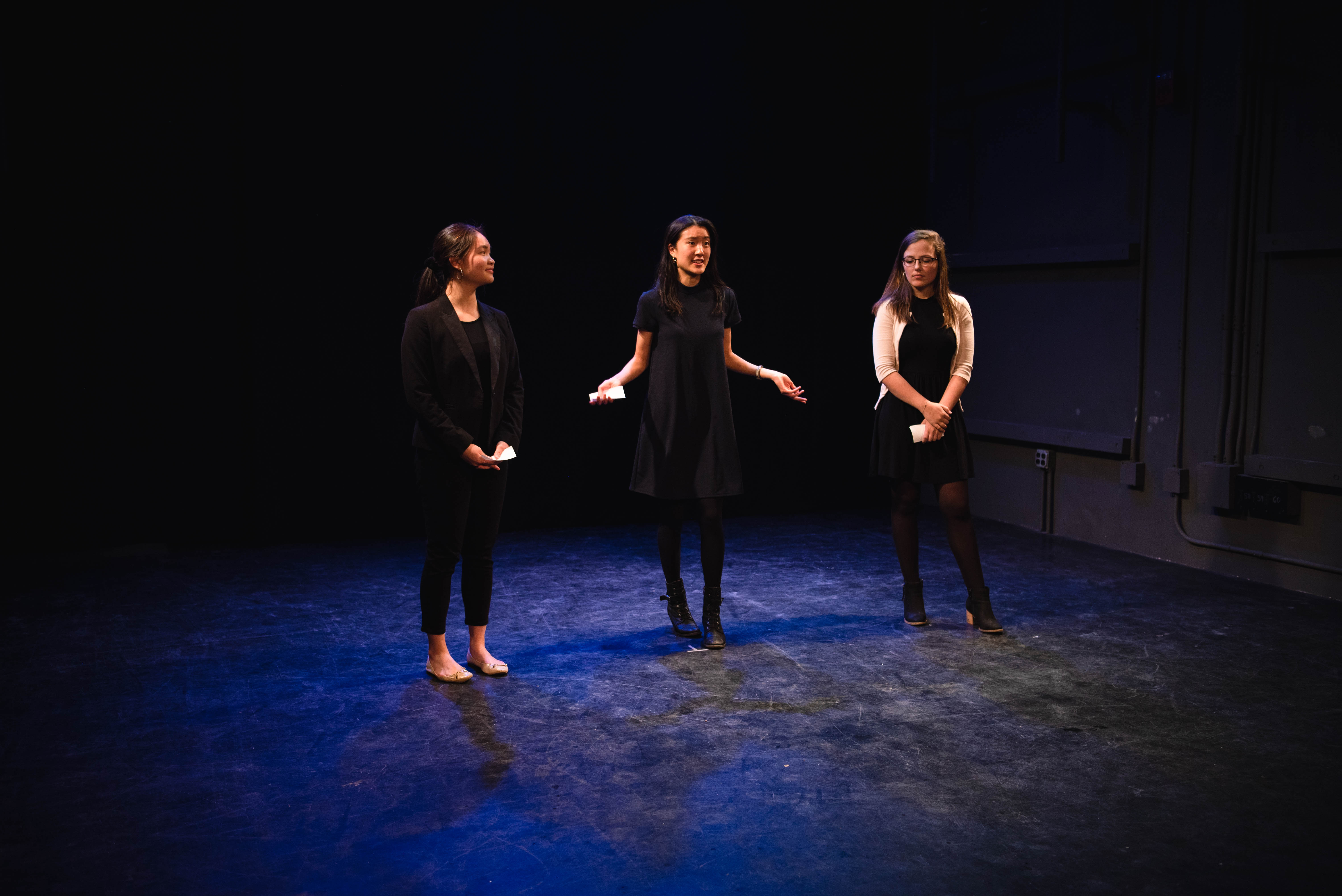 Three students speak on stage