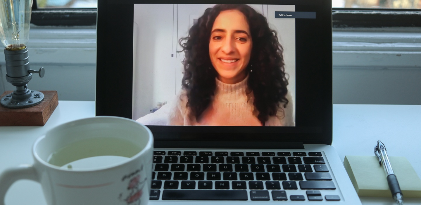 Image of laptop playing Mona Elsayed Zoom talk, on desk with tea and notebook