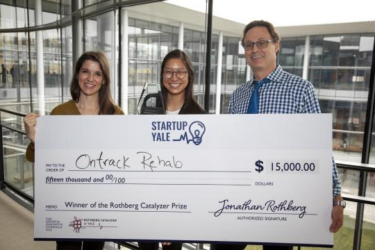Student holds giant check with prize leaders