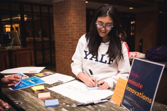 Student in Yale t-shirt writes ideas on paper during pop-up event