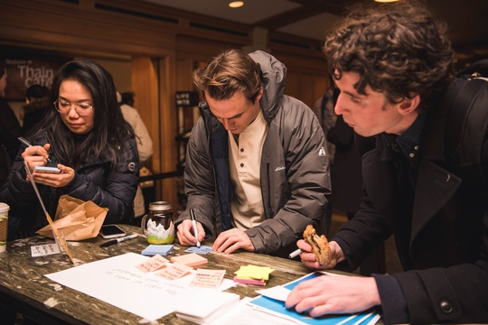Three students write ideas on post-its around table