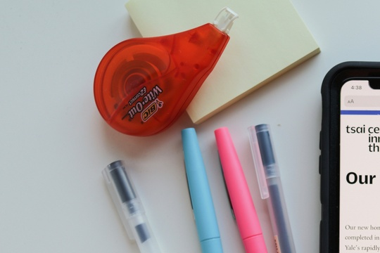 Flatlay image of desk supplies and Tsai CITY website on smartphone