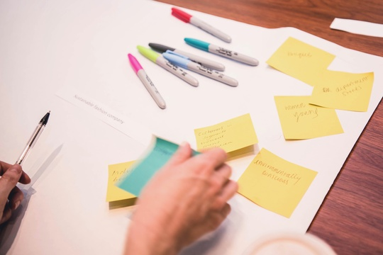 Image of hands with post-its, paper, and pens