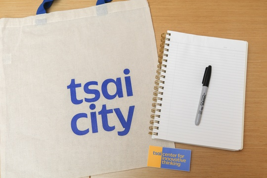 Flatlay image of notebook, pen, and Tsai CITY tote bag and sticker